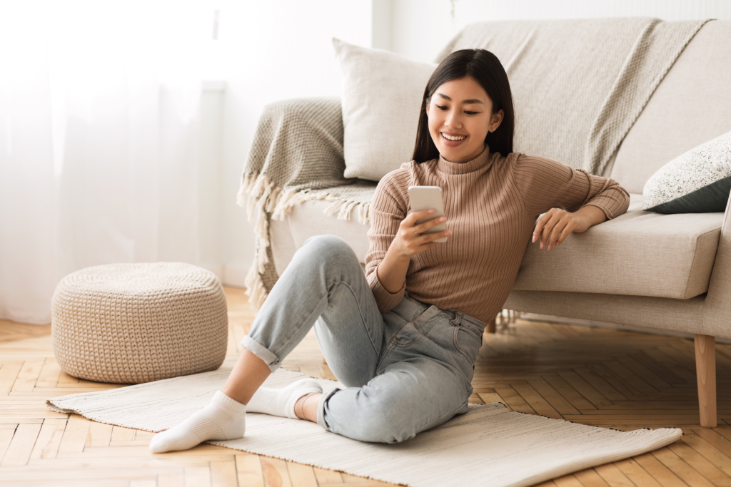 Happy Asian Girl Messaging on Phone at Home